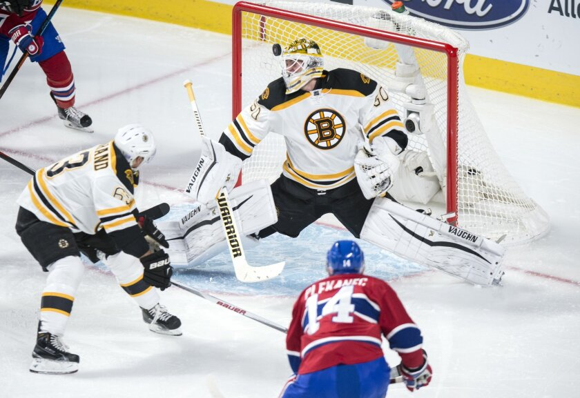 Montreal Canadiens' Tomas Plekanec (14) scores past Boston Bruins' goalie Jonas Gustavsson (50) as teammate Brad Marchand (63) looks on during second period NHL hockey action, in Montreal, on Saturday, Nov. 7, 2015. (Paul Chiasson/The Canadian Press via AP)