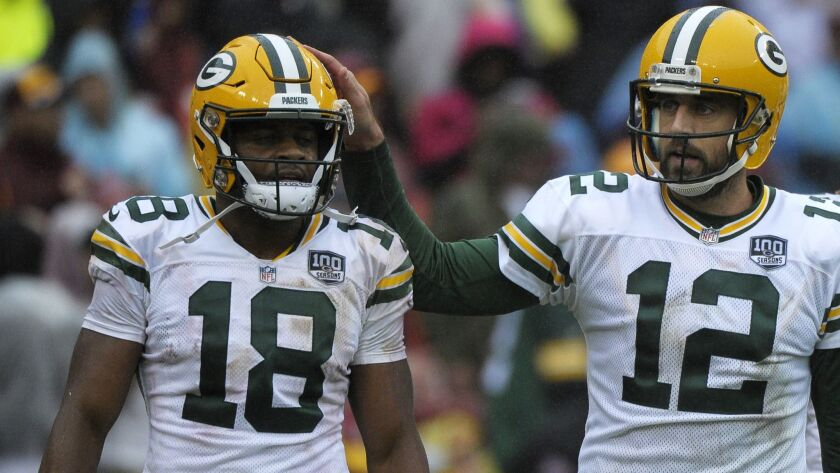 Green Bay Packers quarterback Aaron Rodgers (right) and wide receiver Randall Cobb (left) celebrate a touchdown.