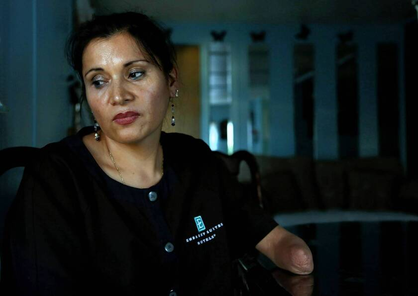 """Argelia Rico, a housekeeper at Embassy Suites in Irvine, says the hotel's management is """"trying to shut me up."""" Though she lacks part of an arm, she changes as many as 25 beds a day, double the workload of her unionized counterparts in L.A. County."""
