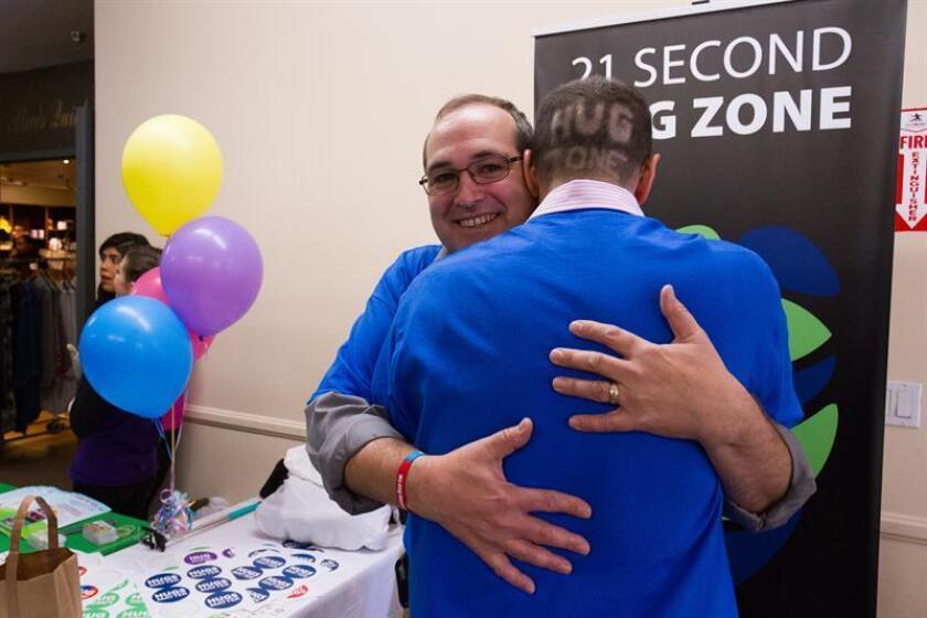 """Kevin Zaborney creador del Día Nacional del Abrazo sostiene un abrazo de 21 segundos con uno de sus colaboradores hoy, 21 de enero de 2018, durante la celebración del Día Nacional del Abrazo en Los Angeles (EE.UU.). Representantes de mas de 42 países intentaron romper el record Guinness del """"Abrazo colectivo con mas personas de diferentes nacionalidades"""" en el 32 aniversario del Día Nacional del Abrazo. EFE"""