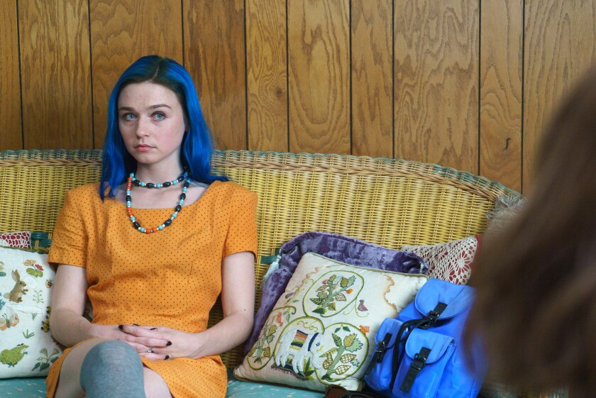 """Jessica Barden sits on a couch in a scene from """"Pink Skies Ahead"""""""