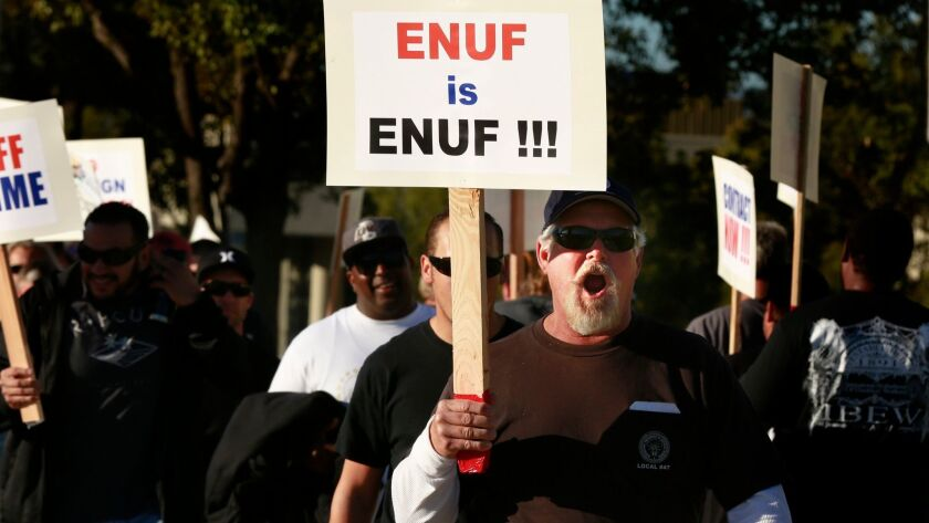 Members of the International Brotherhood of Electrical Workers walk the picket line in front of the Southern California Edison building in Irvine on Feb. 10, 2015, to protest plans by Edison to lay off workers in favor of replacements from India.