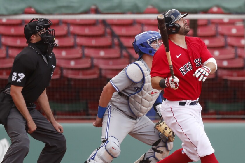 Boston Red Sox's Mitch Moreland, right, watches his two-run, walk-off home run in front of Toronto Blue Jays' Reese McGuire during the ninth inning of a baseball game, Sunday, Aug. 9, 2020, in Boston. (AP Photo/Michael Dwyer)