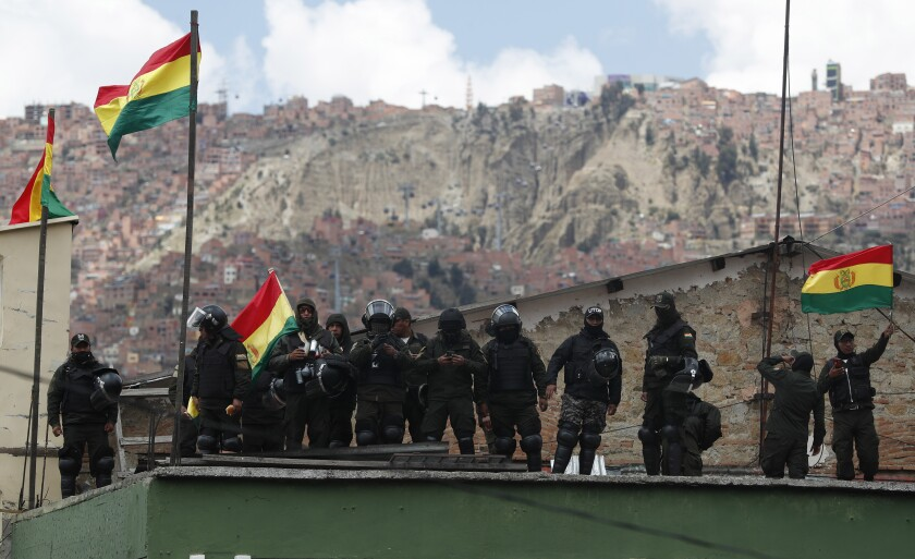 Police against the reelection of President Evo Morales stand on the rooftop of a police station waving national flags just meters away from the presidential palace, in La Paz, Bolivia, Saturday, Nov. 9, 2019. Policemen guarding the exteriors of the presidential palace in La Paz retreated to their barracks on Saturday, while officers in other Bolivian cities have declared mutinies and joined protests against President Evo Morales, who has faced two weeks of unrest over disputed election results. (AP Photo/Juan Karita)