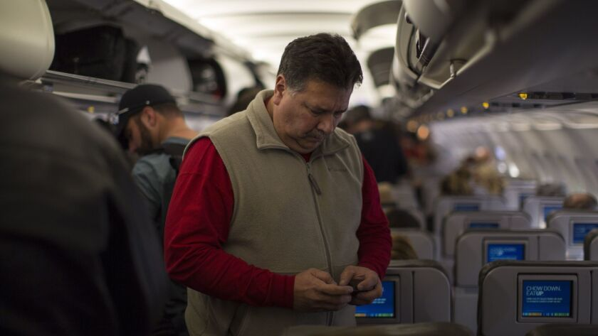 A passenger on Jet Blue Airways checks his cellphone before disembarking at the Long Beach airport. The Department of Transportation has completed accepting public comments on a plan to continue a ban on cellphone calls on planes.
