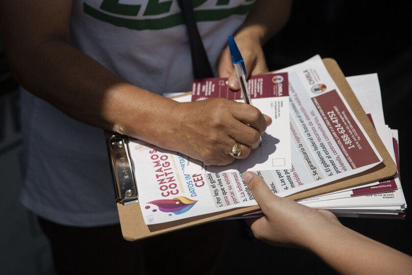 America Barrera, a youth volunteer with CHIRLA, helps Mercedes N. Martinez sign up for the census