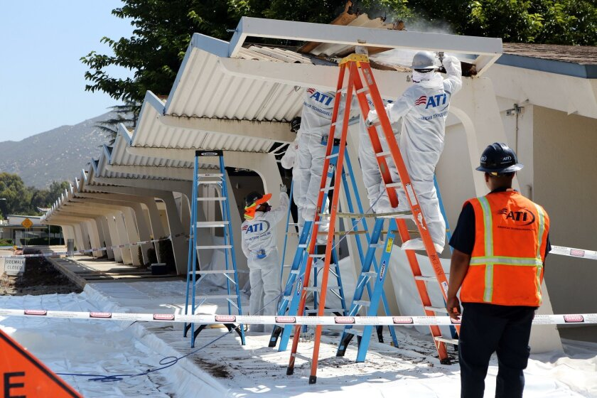 Workers at Orange Glen Elementary School in Escondido replace roofing on canopies Thursday.
