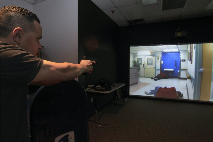 Rich Hinzo, a San Diego police officer a defensive tactics instructor at the San Diego Regional Public Safety Training Institute at Miramar College, demonstrates an active shooter scenario in the Force Option Simulator.