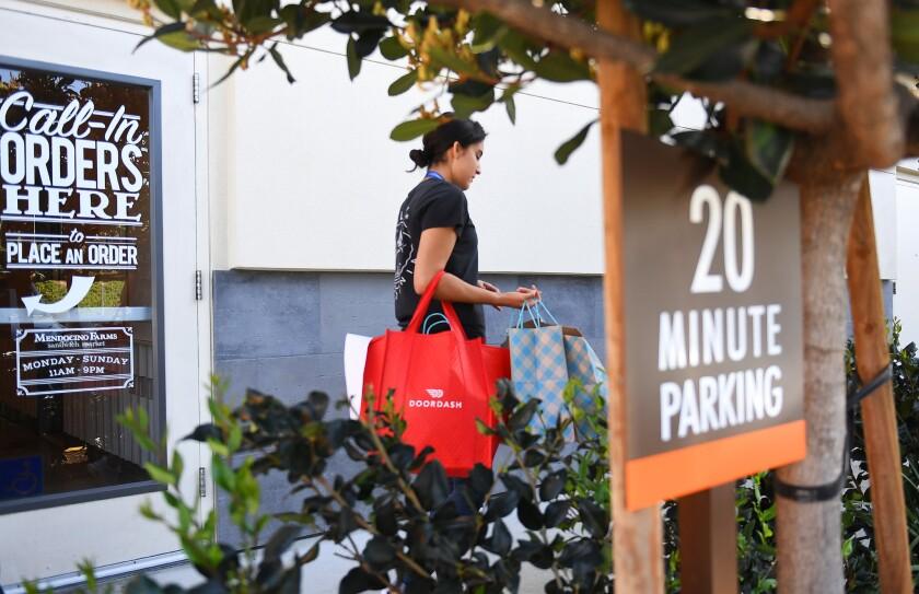 DoorDash deliverer Ricky Sierra picks up an order at Mendocino Farms in El Segundo.