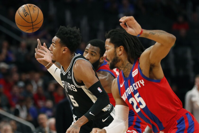 San Antonio Spurs guard Dejounte Murray (5), Detroit Pistons center Andre Drummond, rear, and guard Derrick Rose (25) reach for the loose ball during the first half of an NBA basketball game, Sunday, Dec. 1, 2019, in Detroit. (AP Photo/Carlos Osorio)