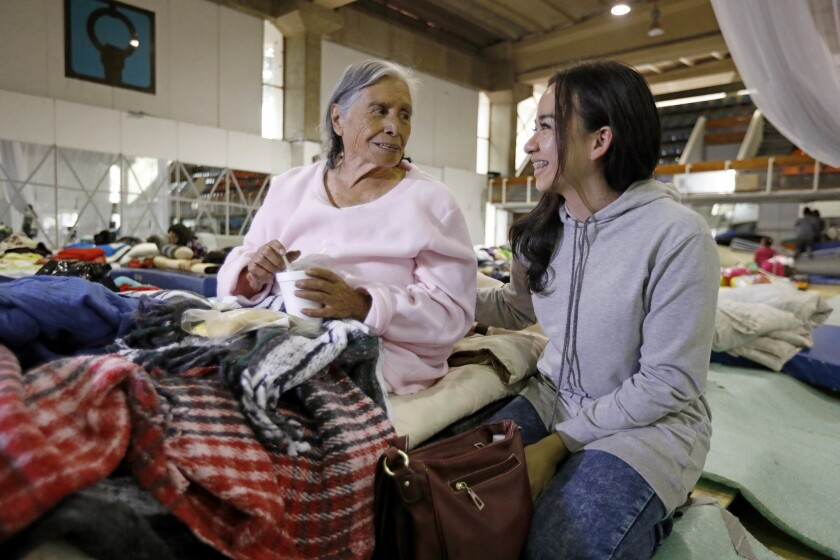 Refugio Gonzalez, 85, left, is comforted by volunteer Lety Rebollar, 19, of Mexico State, in a shelt