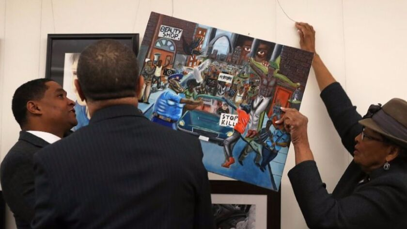 Rep. Cedric Richmond (D-LA),  Rep. William Lacy Clay (D-MO) and Rep. Alma Adams (D-NC)(L-R) re-hang the controversial painting by Missouri student David Pulphus on a tunnel wall at the U.S. Capitol after it was taken down in protest of cops depicted as pigs.