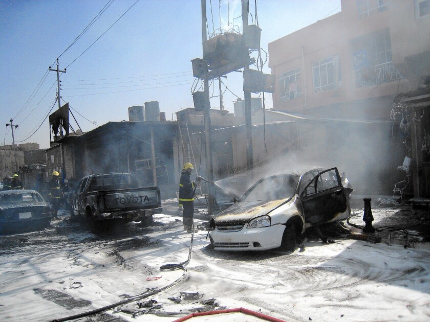 Iraqi firefighters extinguish a car fire, sparked by a motorcycle bomb attack in Kirkuk, Iraq. Recent car bombings have left no doubt that Kirkuk is at risk, both from militants infiltrating from the outskirts and sleeper cells within.
