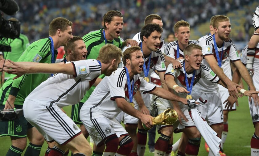 Germany's Mario Goetze, centre, and teammates celebrate with the trophy after the World Cup final soccer match between Germany and Argentina at the Maracana Stadium in Rio de Janeiro, Brazil, Sunday, July 13, 2014. Germany won the match 1-0. (AP Photo/Martin Meissner)