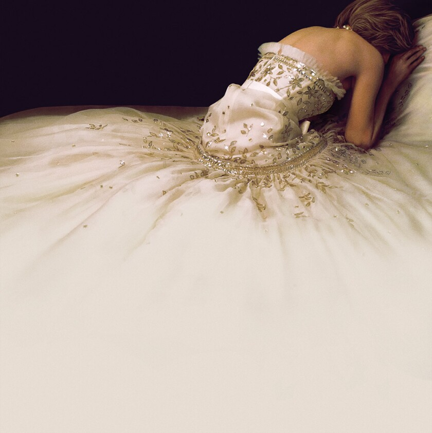 The back of a woman in a white gown leaning over