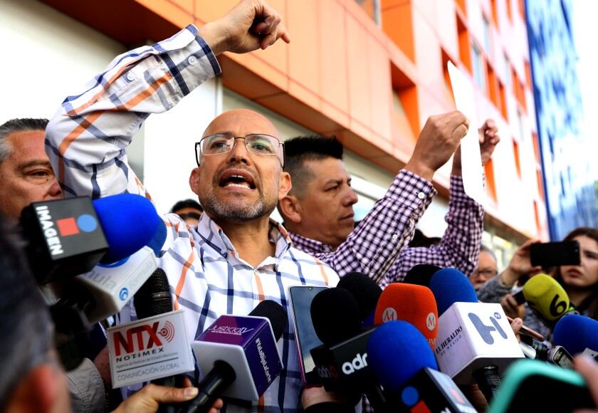 Israel Rivas, left, and Omar Hernandez address the media during a protest Tuesday outside the Children's Hospital in Mexico City.