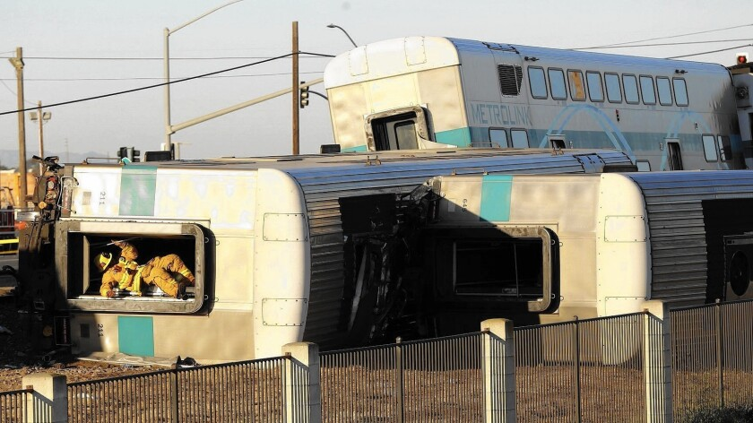 A firefighter climbs out of an overturned Metrolink train car that derailed in Oxnard on Feb. 24.