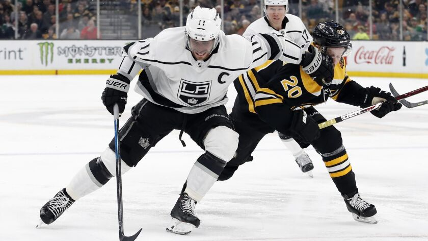 Los Angeles Kings' Anze Kopitar, left, tries to fight off Boston Bruins' Joakim Nordstrom (20) durin
