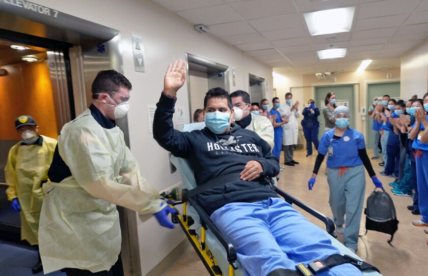 Medical workers salute COVID-19 patient Juan Valdez Cazares as he leaves UC San Diego Medical Center in Hillcrest.