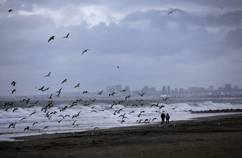 People walk along the coast in Imperial Beach as the first storm of the season moved through the area on Wednesday. Forecasters expect another big storm the middle of next week.