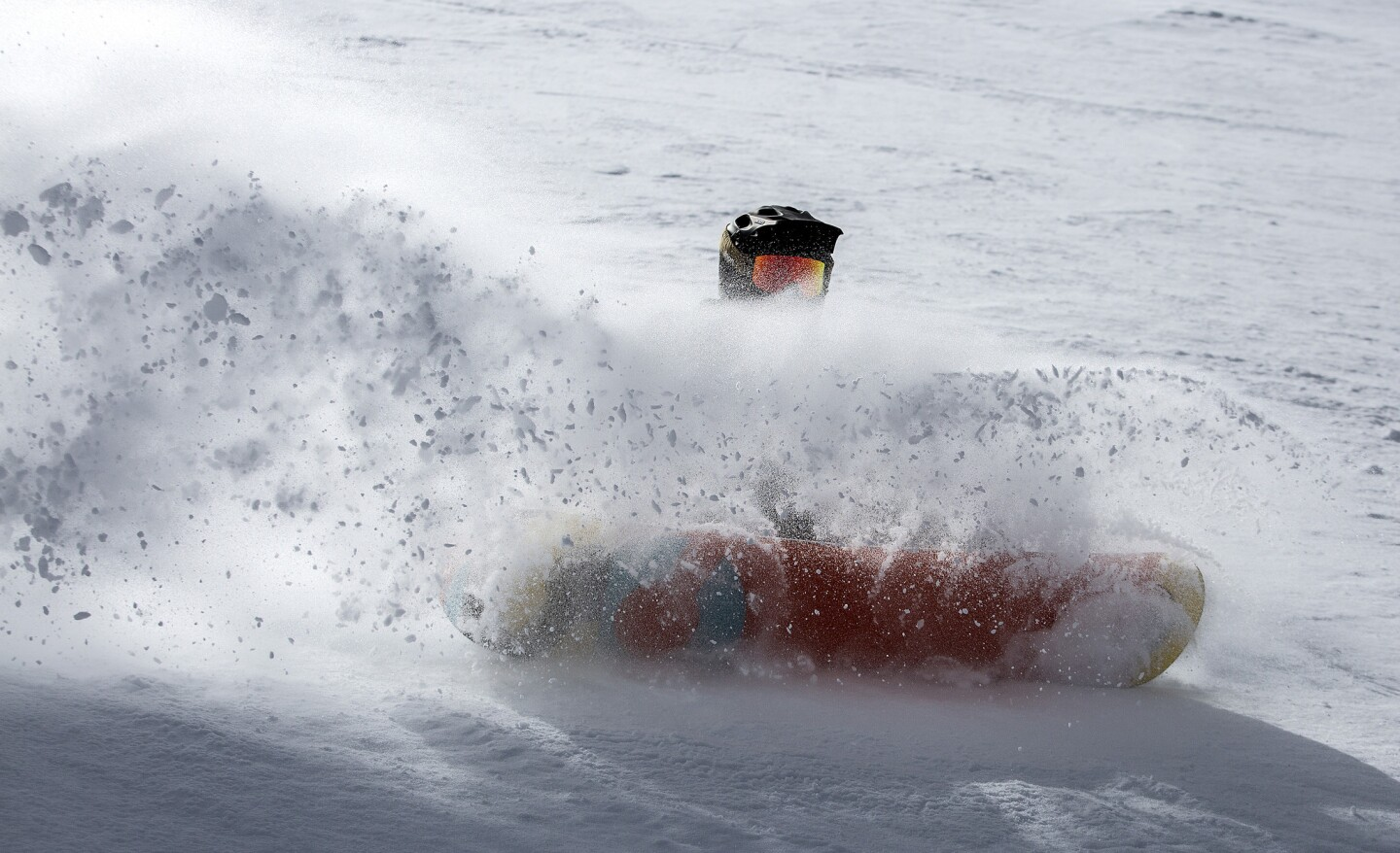 A snowboarder plows through the Cornice Bowl at Mammoth Mountain.