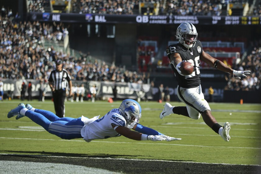 Oakland Raiders running back Josh Jacobs (28) runs for a touchdown past Detroit Lions defensive back Miles Killebrew during the first half of an NFL football game in Oakland, Calif., Sunday, Nov. 3, 2019. (AP Photo/John Hefti)