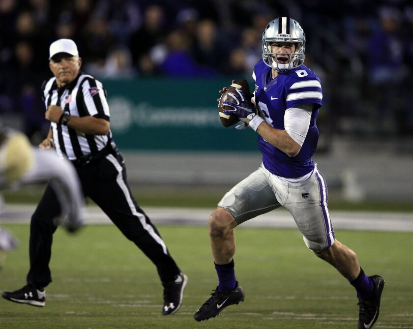 Kansas State quarterback Joe Hubener (8) rolls out with referee Cooper Castleberry, left, during the first half of an NCAA college football game against Baylor in Manhattan, Kan., Thursday, Nov. 5, 2015. (AP Photo/Orlin Wagner)