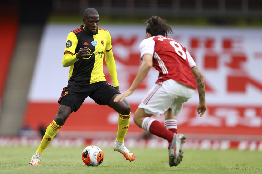 Watford's Abdoulaye Doucoure, left, drives against Arsenal's Dani Ceballos during the second half of the English Premier League soccer match between Arsenal and Watford at Emirates Stadium in London, England, Sunday, July 26, 2020. (AP photo/Julian Finney, Pool)