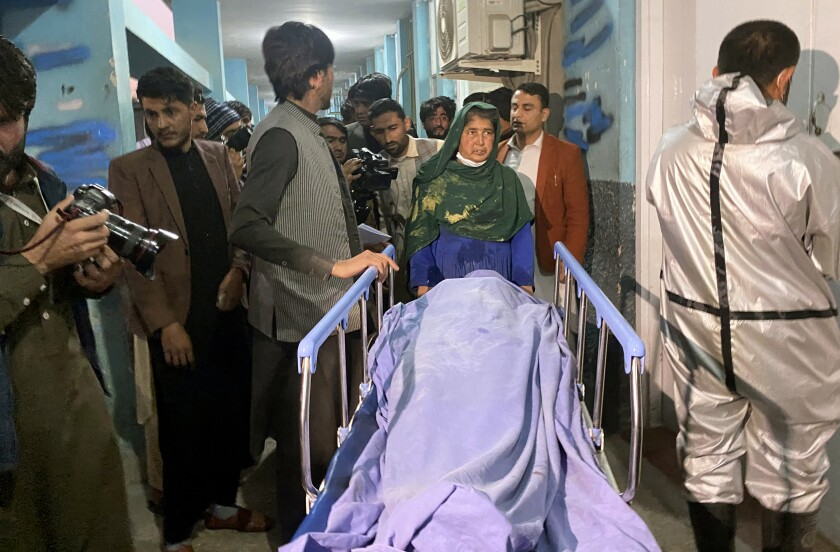 Afghans carry the body of a woman who was killed by gunmen in the city of Jalalabad east of Kabul, Afghanistan, Tuesday, March 2, 2021. Three women who worked for a local radio and TV station in eastern Afghanistan were gunned down Tuesday in two separate attacks, the news editor of the privately owned station said. (AP Photo/Sadaqat Ghorzang)