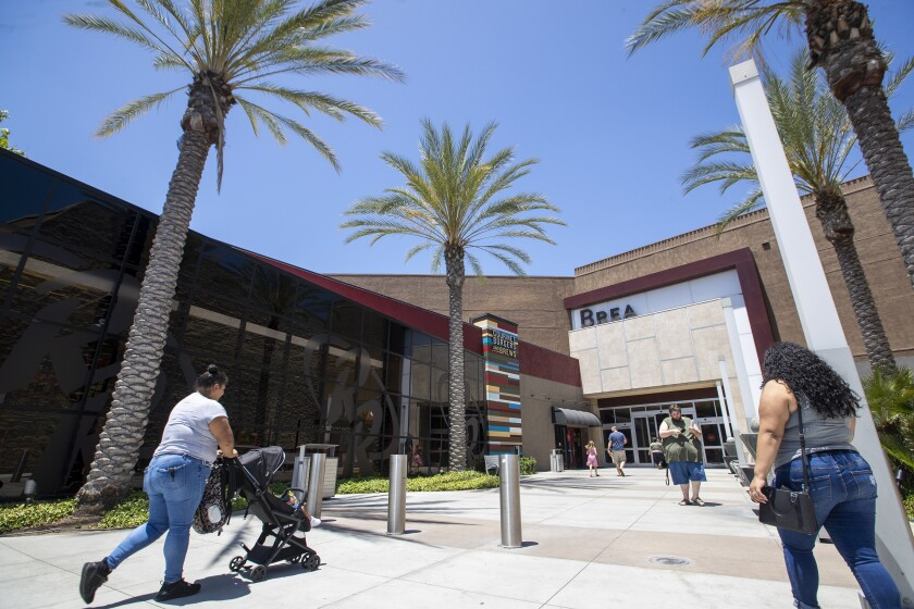 Shoppers come and go from the Brea Mall, which reopened Tuesday.