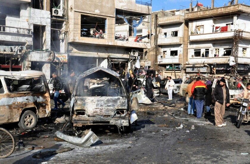 In this photo released by the Syrian official news agency SANA, Syrian citizens gather at the scene where twin bombs exploded at a government-run security checkpoint, at the neighborhood of Zahraa, in Homs province, Syria, Tuesday, Jan 26, 2016. Homs governor Talal Barrazi said on Tuesday that a car bomb, which was followed by a suicide bomber wearing an explosive, killed more than a dozen people and injured many others. (SANA via AP)