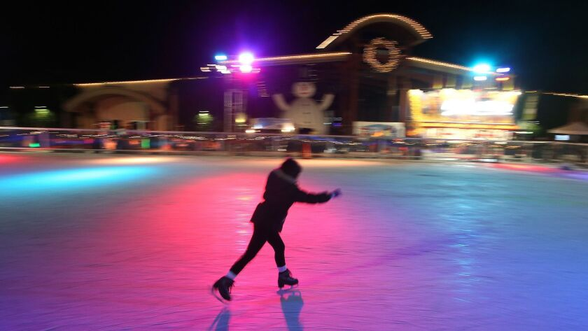 An ice skater takes to the ice under the lights moments before the masses during the 3rd annual Wint