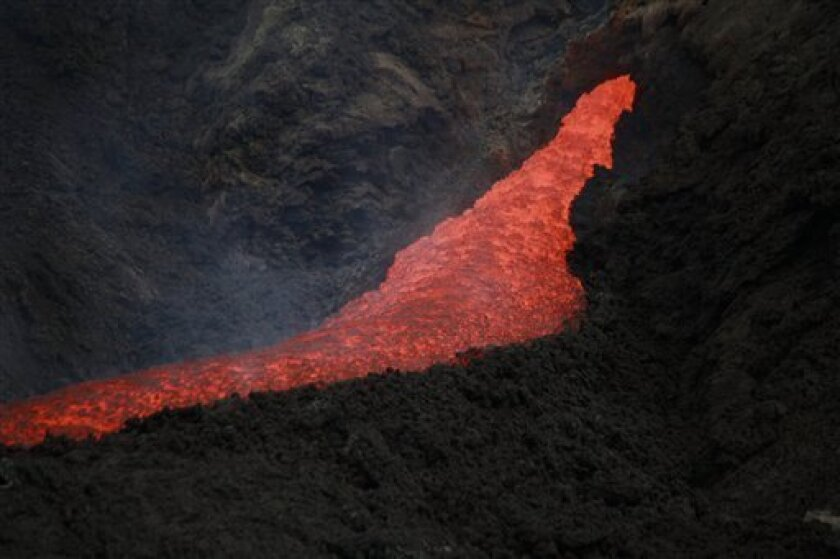 A river of lava flows from the erupting Pacaya volcano in Villa Canales, 50 kms south of Guatemala City, Saturday, June 5, 2010. The volcano started erupting lava and rocks last May 27, forcing thousands of people to flee their homes and disrupting air traffic as ash drifted over major cities. (AP