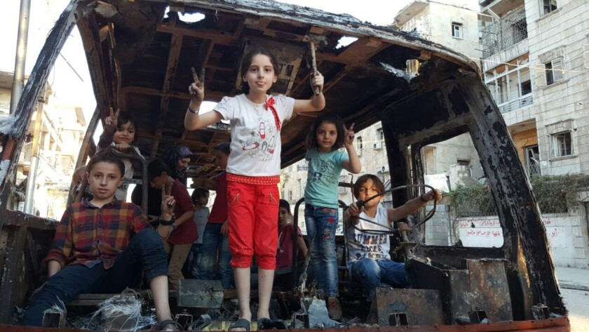 Teacher Afraa Hashem's children and students play in the burned-out remains of a bus.