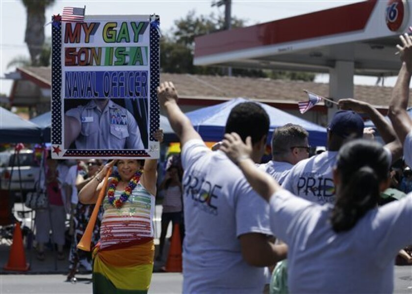 Betty Ayala salutes a group of veterans as she holds a sign showing her son during the gay pride parade Saturday, July 21, 2012, in San Diego. For the first time ever, U.S. service members marched in a gaypride event decked out in uniform Saturday, after a recent memorandum from the Defense Depart