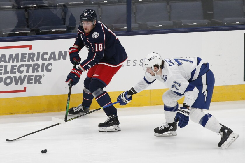 Columbus Blue Jackets' Pierre-Luc Dubois, left, carries the puck up ice against Tampa Bay Lightning's Anthony Cirelli during the first period of an NHL hockey game Thursday, Jan. 21, 2021, in Columbus, Ohio. (AP Photo/Jay LaPrete)
