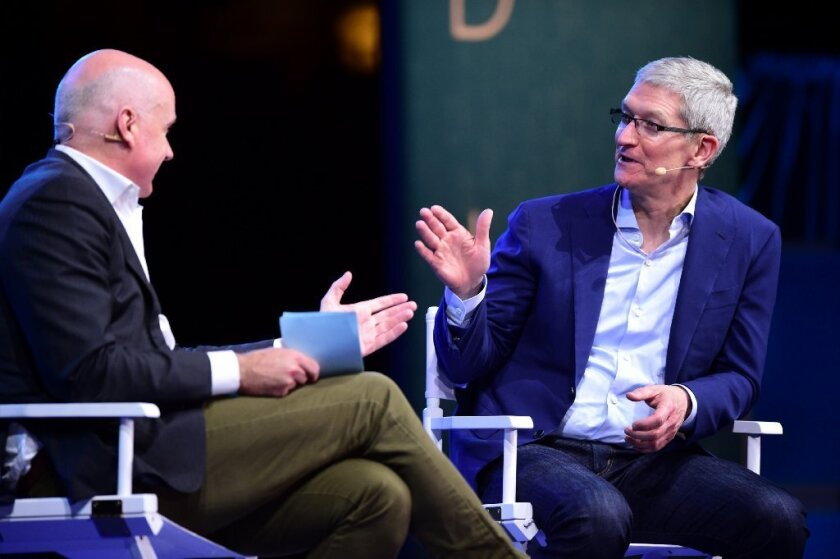 Apple Chief Executive Tim Cook, right, during a Q&A in Laguna Beach on Monday.