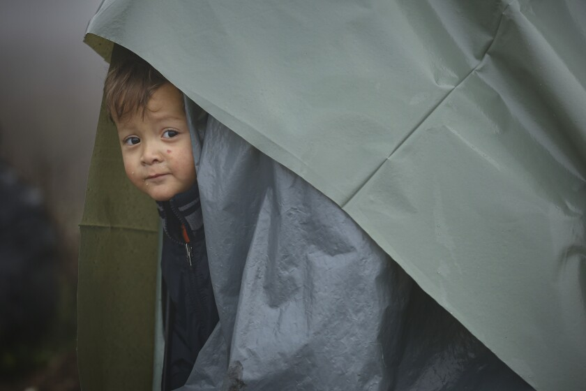 A migrant child peers from a makeshift tent at a camp housing migrants mostly from Afghanistan in Velika Kladusa, Bosnia, Tuesday, Oct. 12, 2021. Hundreds of migrants _ including small children, babies and elderly people _ have set up a new improvised camp in northwest Bosnia, determined to brave worsening weather and tough Croatian border police for a chance to reach Western Europe.(AP Photo)