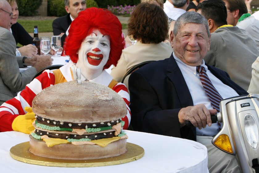 Big Mac creator Jim Delligatti is joined by Ronald McDonald at his 90th birthday party in 2008, featuring a giant Big Mac birthday cake.
