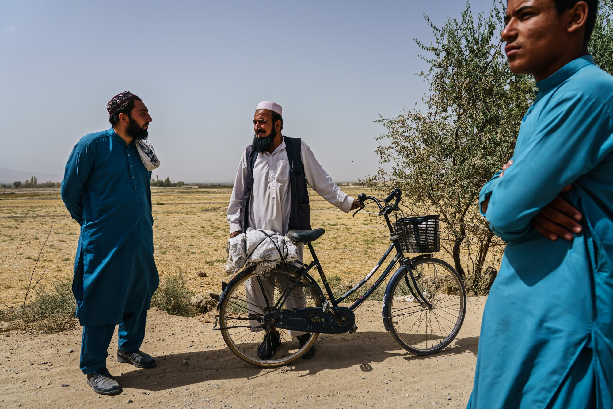 A man with a bicycle talks to two others on a rural road with an empty field in the background.