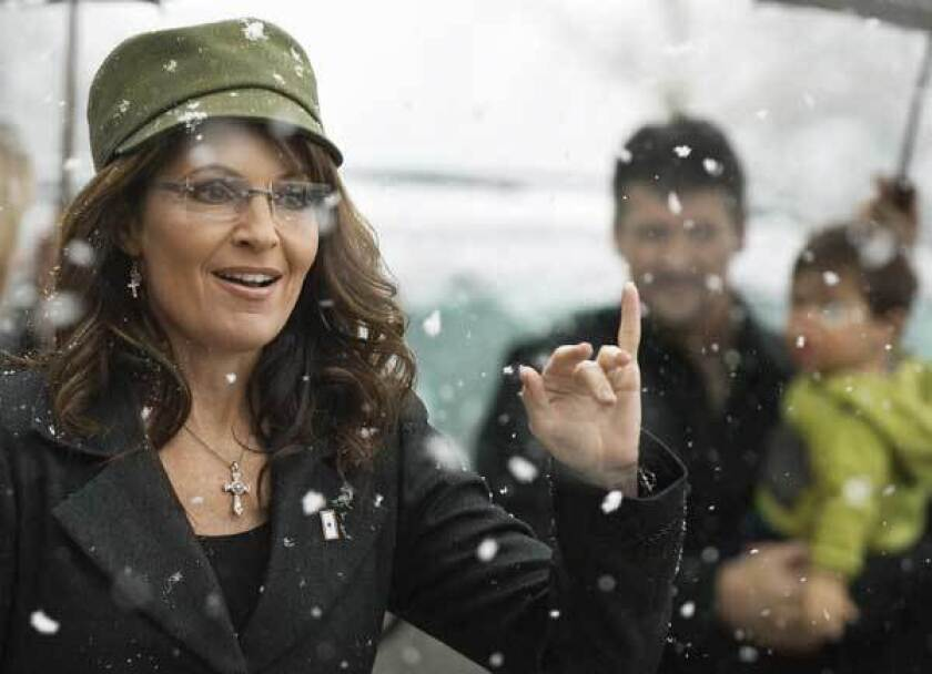 Former Alaska governor and Republican vice presidential nominee Sarah Palin arrives with her husband Todd and son Trig.