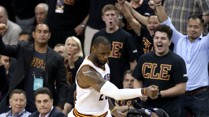 Cavaliers forward LeBron James celebrates, along with fans, after scoring against the Warriors in the second half of Game 6 on Thursday night.