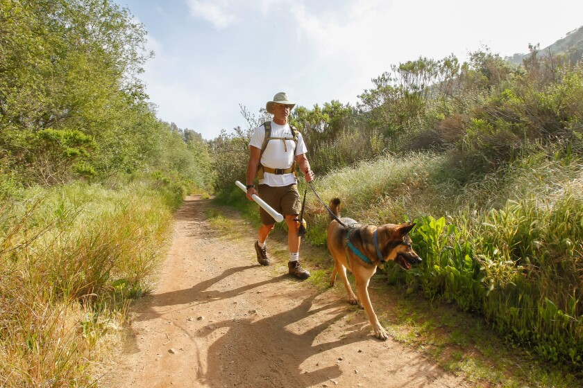 Lance Cummings hikes with his dog, Buddy, on Thursday in San Elijo Hills area of San Marcos. Cummings is training for a fundraising trek across Greece in May that will re-create the epic journey of the Spartan army in 480 BC.
