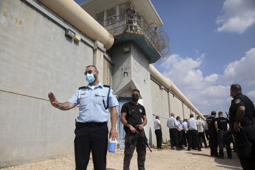 Police officers and prison guards stand outside prison walls.