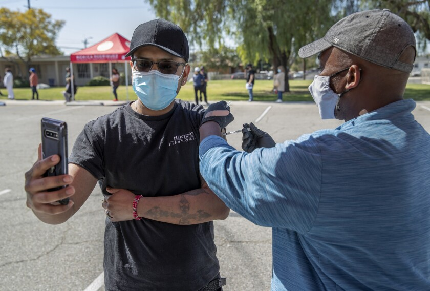 Man takes a video as he receives COVID-19 vaccine in Pacoima