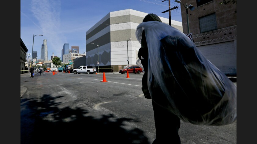 A homeless man walks along 5th Street in downtown Los Angeles with his possessions on his back after a cleanup program on skid row.