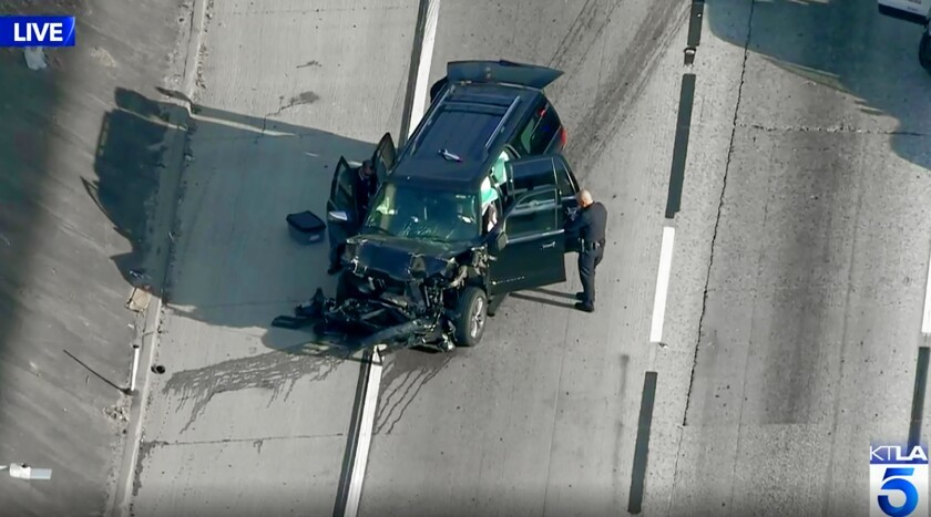 This photo from KTLA-TV video shows a Los Angeles police officer at the scene following a pursuit of a hearse on Interstate 110 in south Los Angeles, Thursday, Feb. 27, 2020, after it was stolen late Wednesday. The Lincoln Navigator was stolen from outside a Greek Orthodox church in East Pasadena, Calif., on Wednesday night. The Los Angeles County Sheriff's Department says one person is in custody. Local media have reported that the body was left in the vehicle while a mortuary attendant brought a different body into the church and that's when the vehicle was stolen. (AP Photo/KTLA-TV via AP)