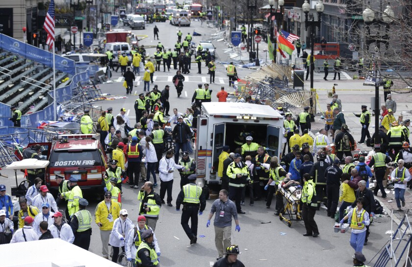 FILE— In this Monday April 15, 2013 file photograph, emergency workers aid injured people at the finish line of the 2013 Boston Marathon following two explosions in Boston. Mass. Boston is marking eight years since the bombing at the 2013 Boston Marathon killed three people and injured scores of others. Acting Mayor Kim Janey on Thursday, April 15, 2021, paid a noontime visit to the downtown memorial marking the bombing site. (AP Photo/Charles Krupa, File)