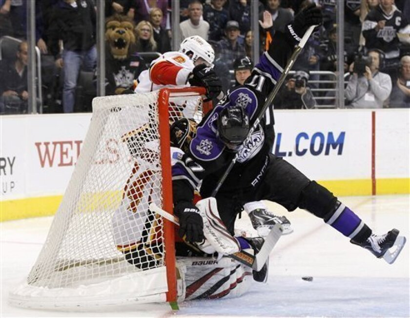 Los Angeles Kings' Wayne Simmonds, right, collides with Calgary Flames goaltender Miikka Kiprusoff of Finland as Flames' Cory Sarich defends during the second period of an NHL hockey game in Los Angeles on Monday, March 21, 2011. (AP Photo/Danny Moloshok)