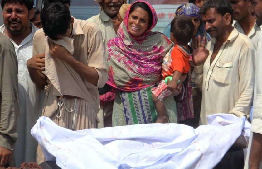Relatives weep over a body at a hospital in Bahawalpur, Pakistan, after the oil truck fire.